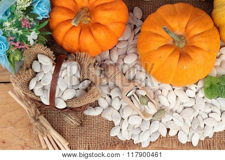 Pumpkin With Pumpkin Seeds On Wood Background.