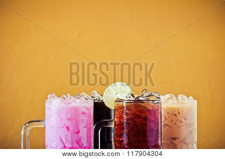 Set of different Asian soft drink Thai iced lemon tea Thai iced black tea Thai iced milk tea Thai iced black coffee and Thai Iced Pink Milk on table