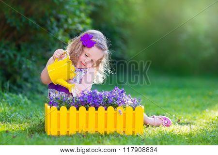 Little Girl Watering Farden Flowers