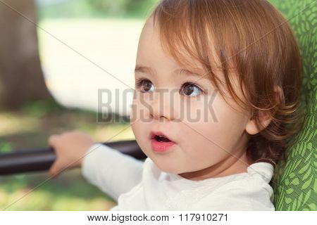 Happy Toddler Girl Swinging On A Swing