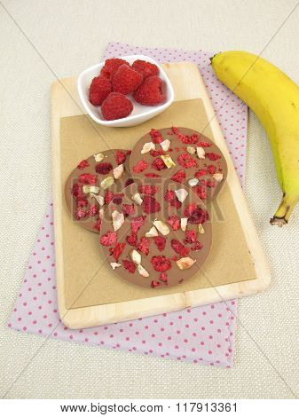 Homemade chocolate coins with raspberry and banana