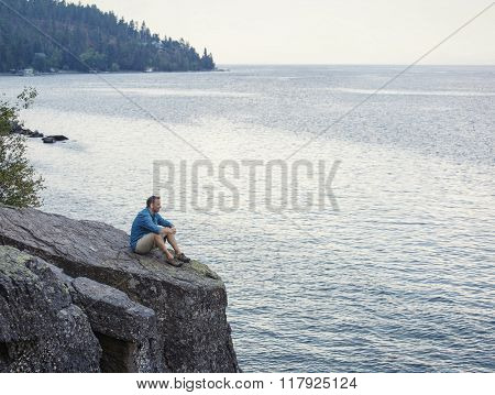 Middle aged man sitting on the edge of cliff overlooking a beautiful ocean bay thinking, meditating and praying