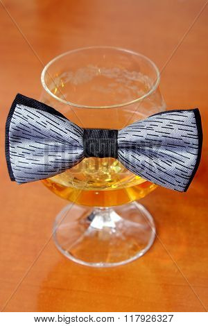 Gray And Black Bow Tie On A Glass Of Cognac With Red Rose