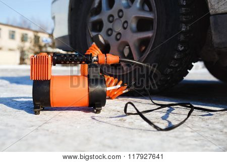 Car air compressor in working position at snow. Self-inflating wheels, automobile tire pressure cont