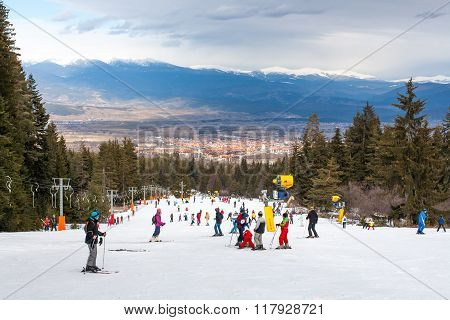 Skiers on the slope , ski lift, mountains view and Bansko panorama, Bulgaria