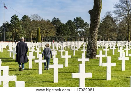 COLLERVILLE SUR MER - APRIL 6: people walking among the crosses on April 6, 2015 in Collerville sur