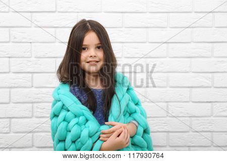 Little girl wrapped in blanket on a white brick wall background