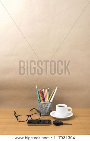 coffee, phone, eyeglasses, color pencil and car key on wood table background