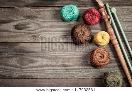 Balls Of Colored Iris Yarn On Wooden Boards