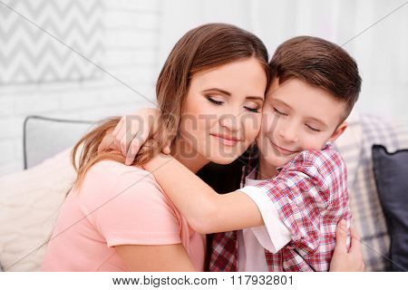 Happy mother with her son sitting on sofa in the room