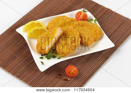 plate of breaded turkey breast on brown place mat - close up