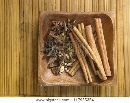 assorted spices in a wooden tray