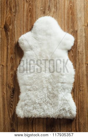 sheepskin carpet on wooden background