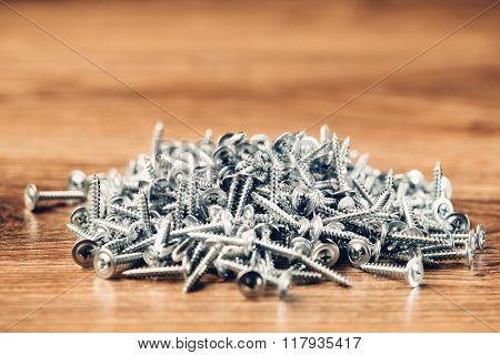 screws fasteners hardware heap on wooden background