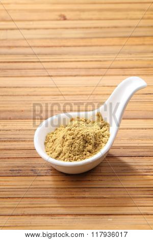cumin powder in saucer on the bamboo background