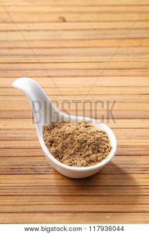 coriander powder in saucer on bamboo background