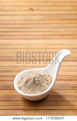 pepper powder in the saucer on the bamboo background