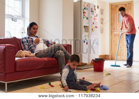 Father Mops Floor As Pregnant Mother Relaxes On Sofa