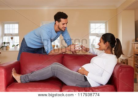 Pregnant Woman Relaxes On Sofa As Man Brings Her Hot Drink