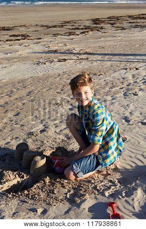 Portrait Of Boy Making Sandcastle On Beach