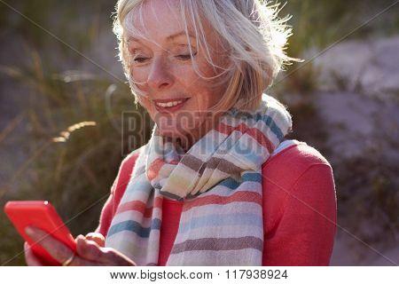Senior Woman On Beach Sending Text Message