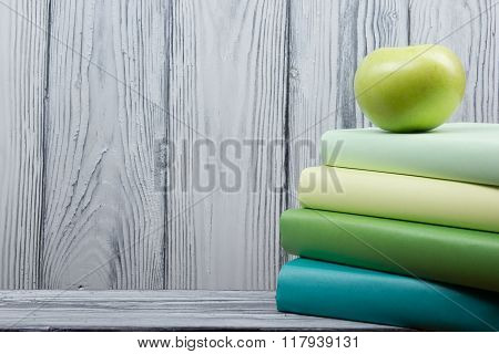 Stack of colorful books and green apple on wooden table. Back to school. Copy space