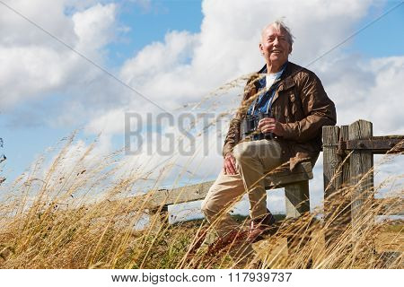 Senior Man With Binoculars Sitting On Wooden Gate