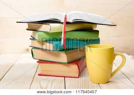 Stack of colorful books, open book and cup on wooden table. Back to school. Copy space