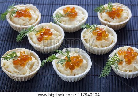 Tartlets with cream cheese and red caviar close up on the black background.