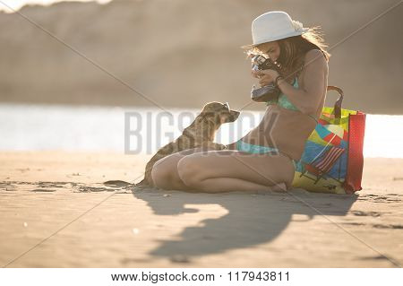 Young woman playing with dog pet on beach during sunset.Woman making photo of puppy posing