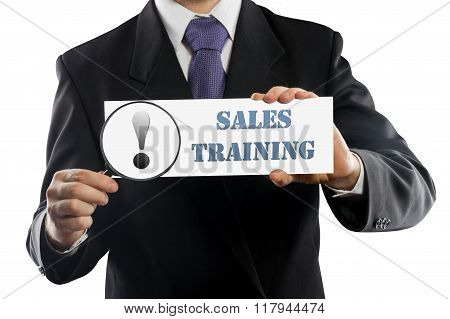 Close up businessman or salesman holding in hands magnifying glass and paper with Sales training mes