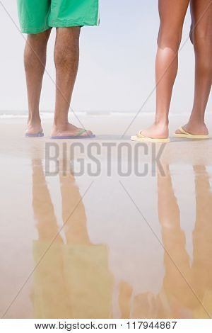 Two people standing on a beach