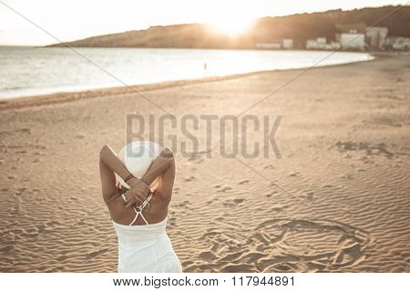 Summer beach fashion woman enjoying summer and sun,walking the beach,watching the sunset/sunrise