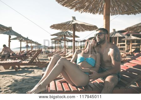 Happy romantic couple enjoying beautiful sunny day at the beach.Couple in hug relaxing on loungers