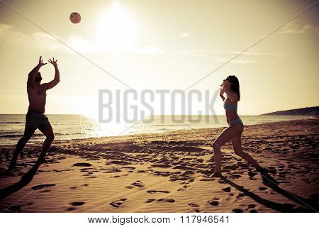 Living healthy active fitness lifestyle doing sport on beach.Couple playing volleyball on the beach