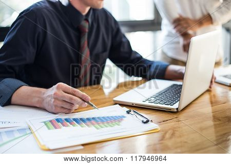 Business Documents On Office Table And Graph Business With Social Network Diagram And Man Working In