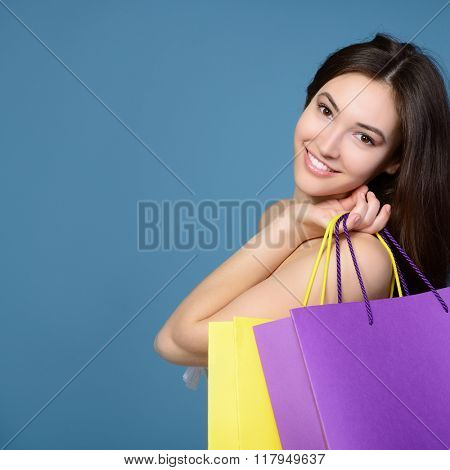 beautiful teen girl with colored sale shopping bags over blue background