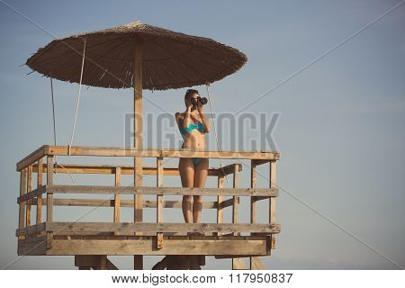 Happy woman photographer on vacation shooting.Photographer ready to take sea landscape pictures with dslr camera on the beach.Professional travel photography.Summer memories.Capturing moment of life