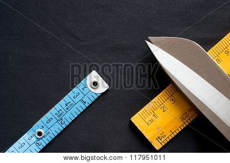 Measuring tape, scale and scissors on black cloth
