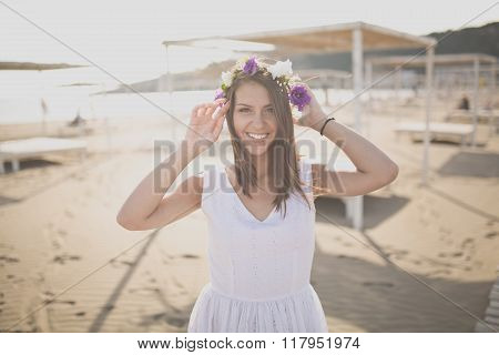 Summer beach fashion woman enjoying summer and sun, walking the beach with flower hat