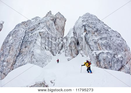 Two Climbers Approach To A Winter Steep Face