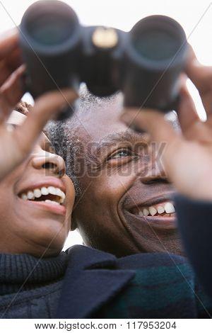 One couple looking through binoculars
