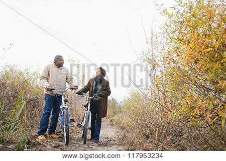 the couple pushing bicycles