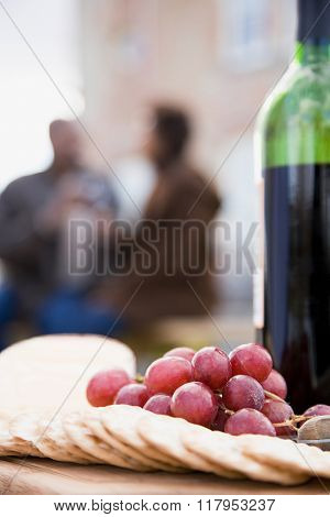 Crackers grapes and a bottle of wine