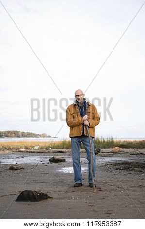 Mature man leaning on a stick