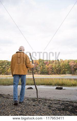 Mature man walking using a stick