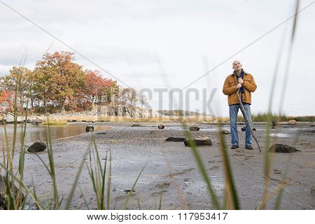 Thoughtful man standing with a stick