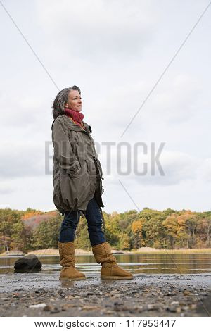 Mature woman standing near a lake