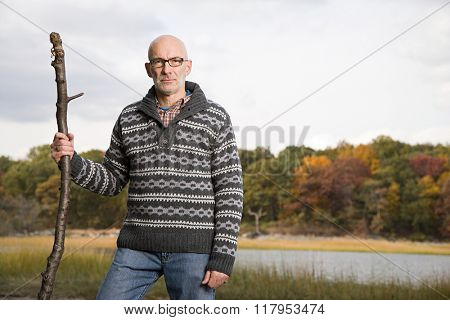 Mature man holding a stick