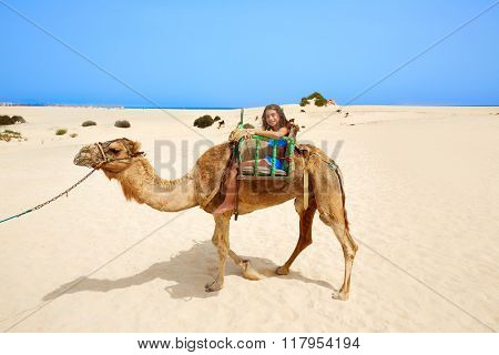 Girls riding Camel in Fuerteventura desert at Canary Islands of Spain